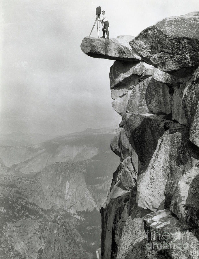 Photographer Standing On Mountain Ledge Photograph by Bettmann
