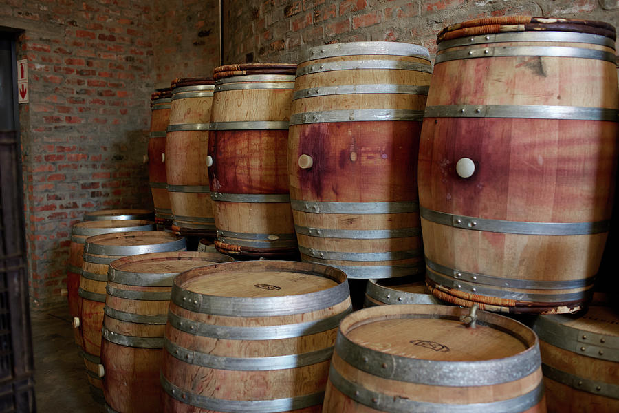 Pile Of Wooden Barrels At Winery Photograph by Klaus Vedfelt