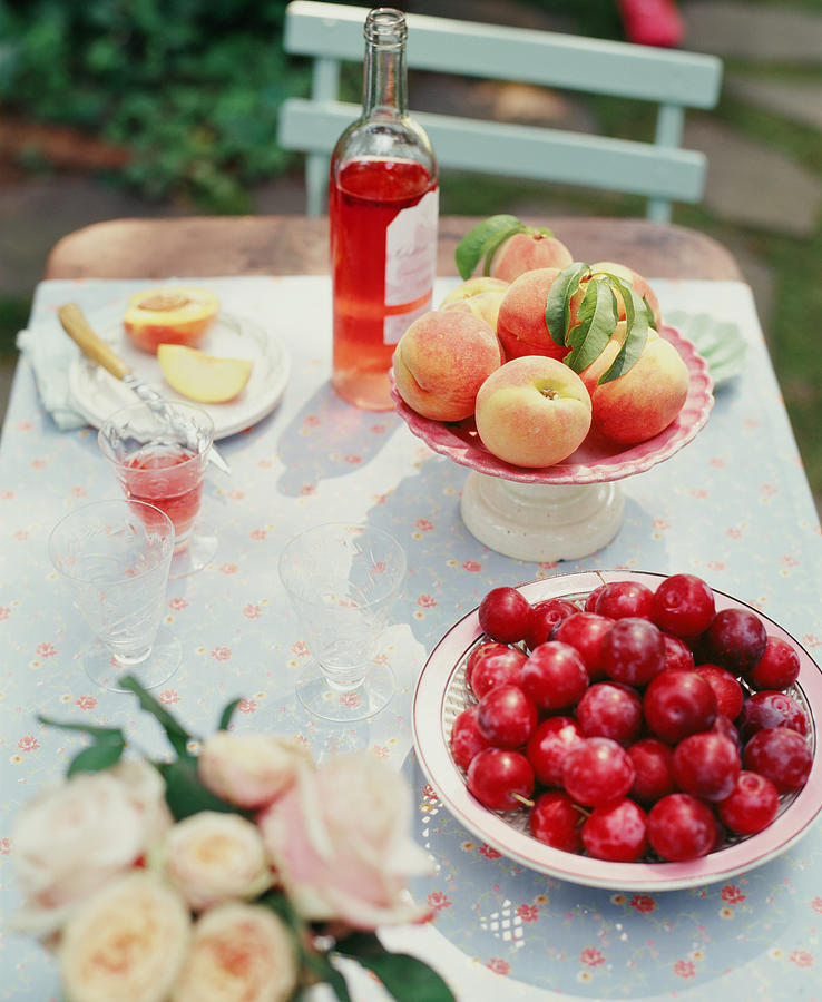 Plums, Peaches, Wine And Flowers On A Photograph by Victoria Pearson