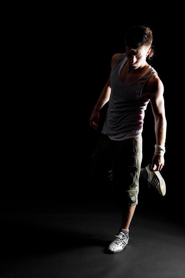 Portrait Of A B-boy Stretching Photograph by Halfdark