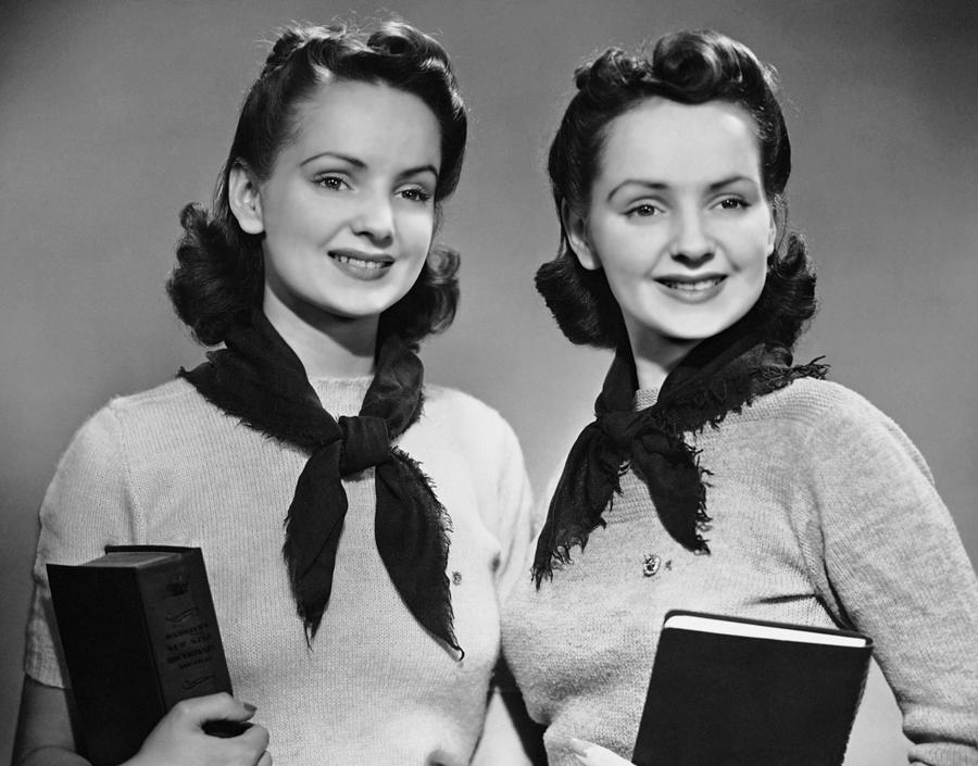 Portrait Of Teenaged Twin Girls Holding Photograph by George Marks
