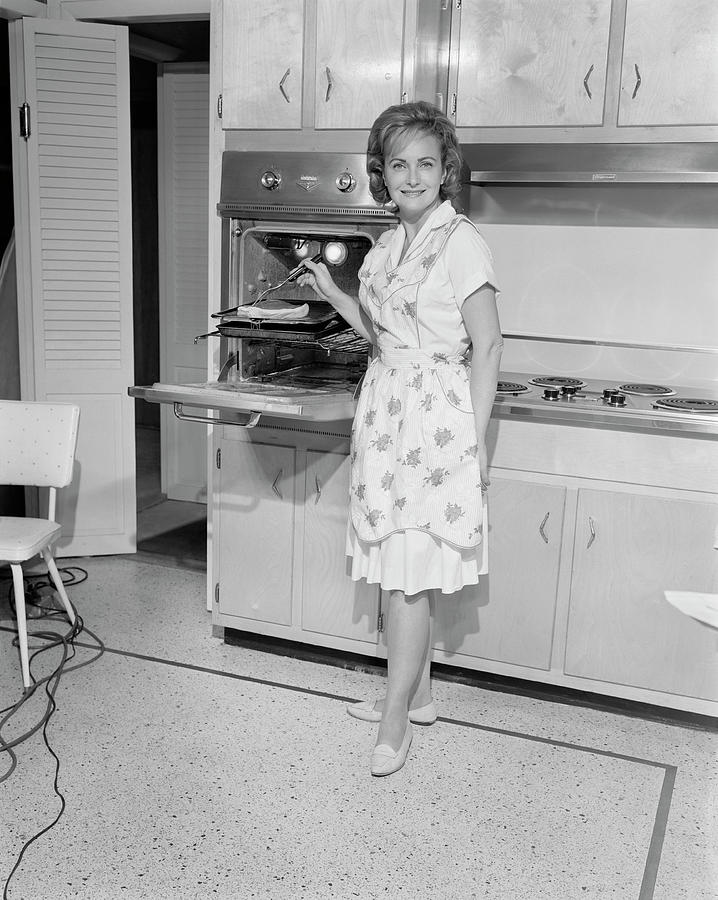 Portrait Of Woman Cooking In Kitchen Photograph by George Marks