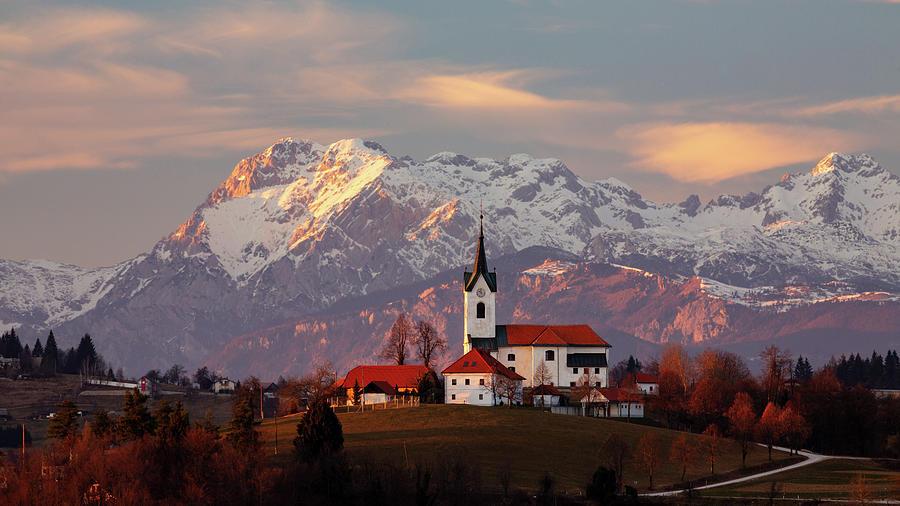 Prezganje church with snowy Kamnik Alps in the background. by Ian Middleton