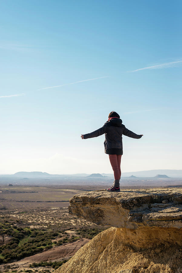 Rear View Of A Woman On Top Of A Hill Standing With Extended Arms While Looking Away Photograph by Cavan Images
