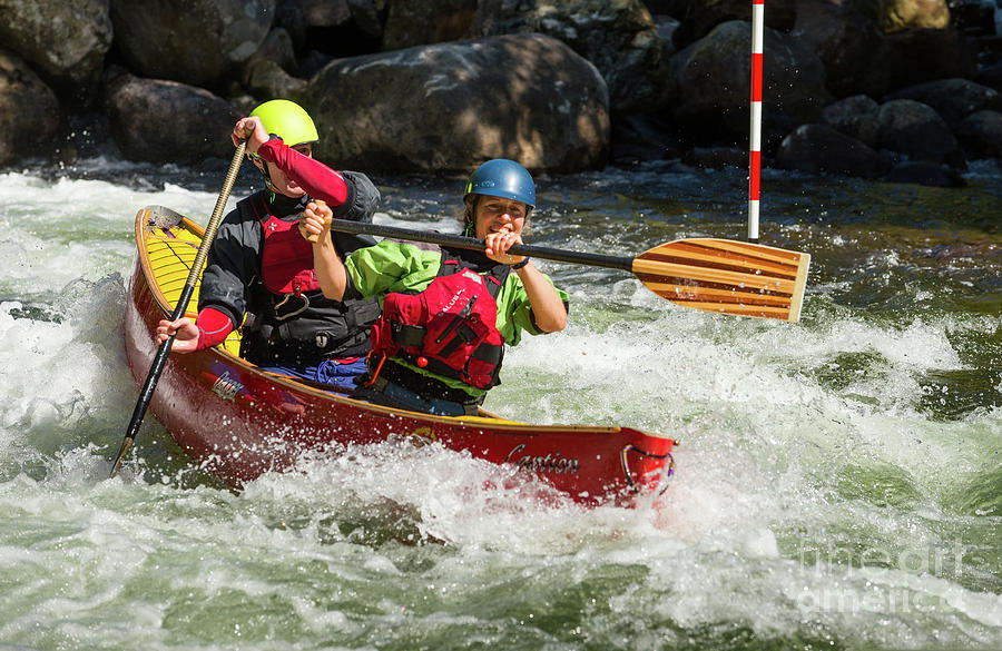 Red canoe riding the rapids by Les Palenik