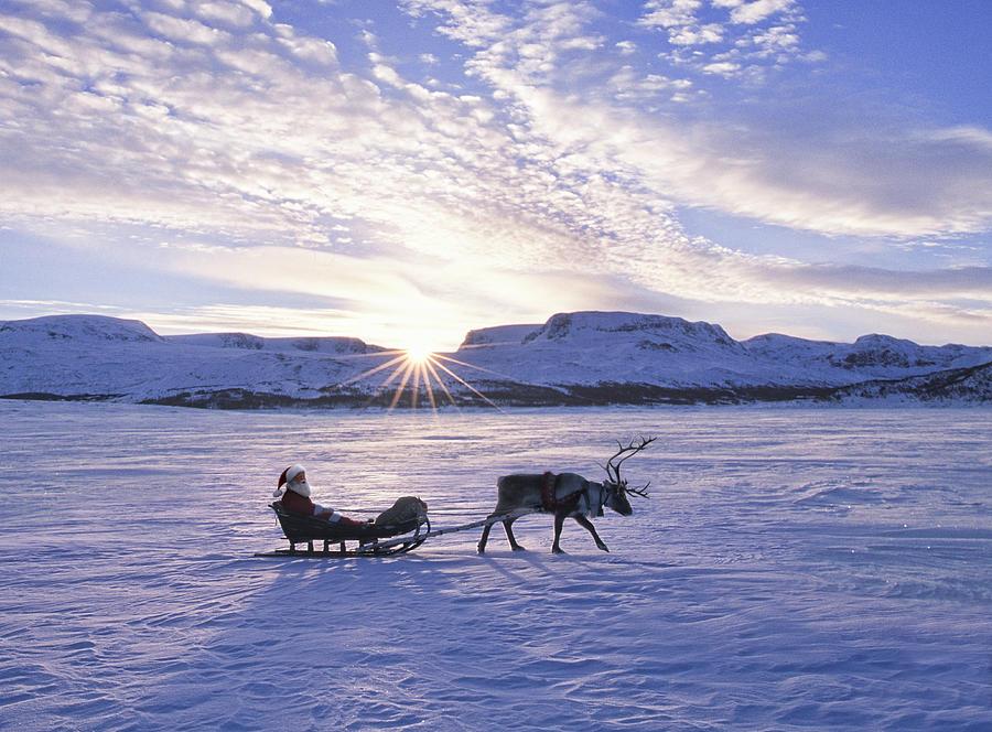 Reindeer Pulling Santa On Sled Over Photograph by Per Breiehagen
