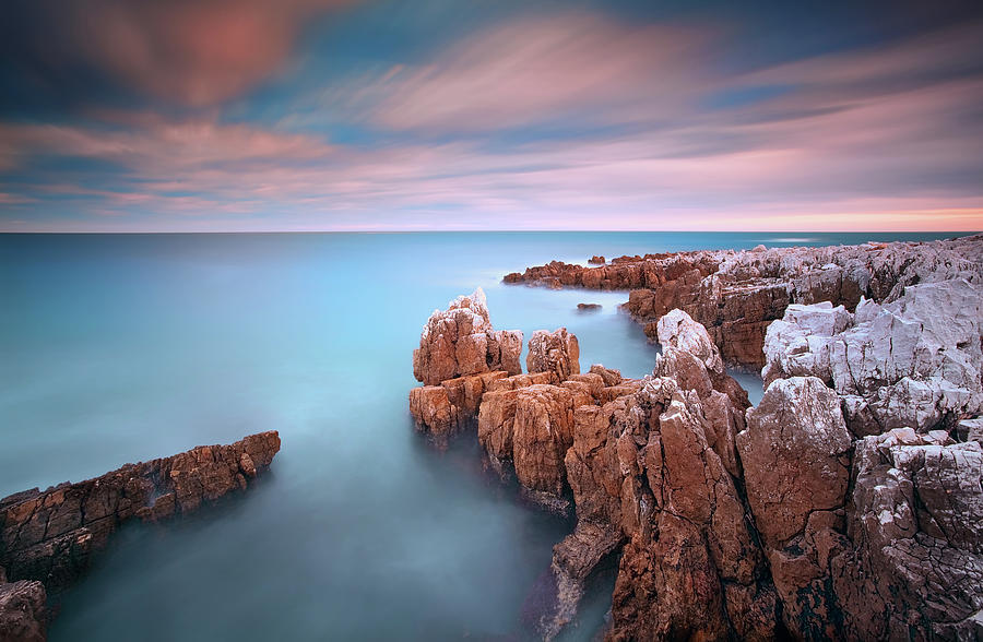 Rocks In Sea At Sunset Photograph by Eric Rousset