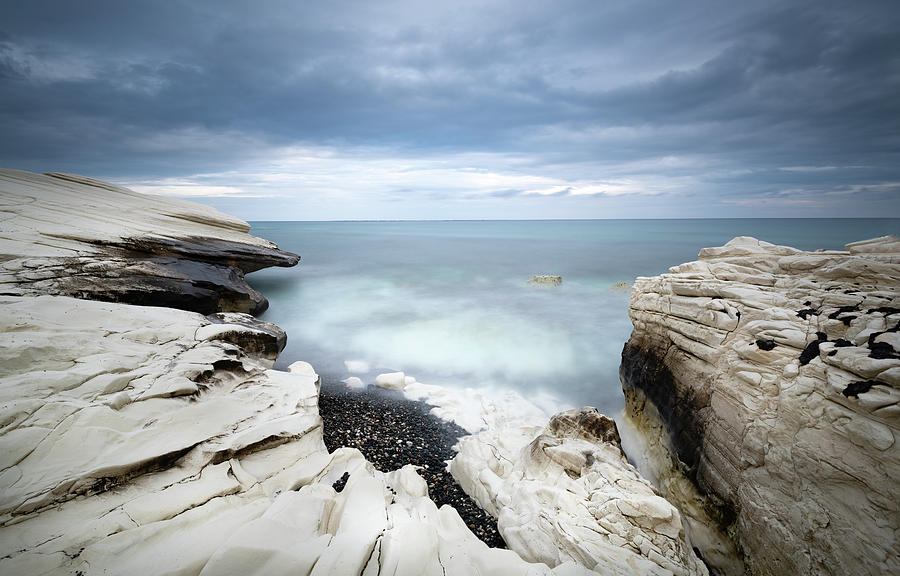 Rocky coast with white limestones and cloudy sky by Michalakis Ppalis
