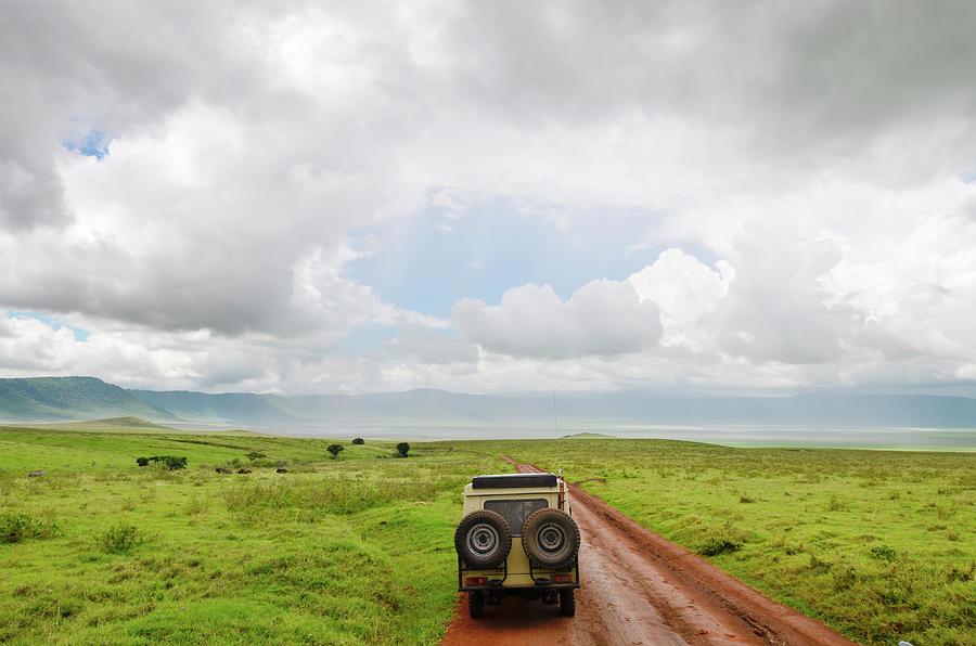 Safari Vehicle W Tourists In Ngorongoro Photograph by Volanthevist