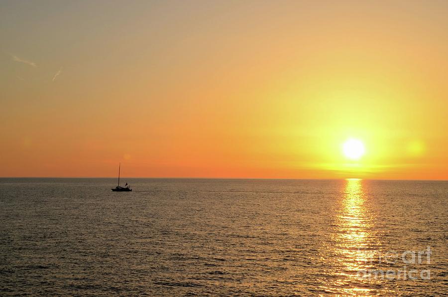 Sail boat cruises on Black Sea as sun sets on horizon Batumi Georgia by Imran Ahmed