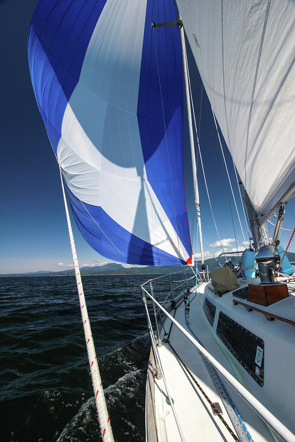 Sailboat Underway with Colorful Spinnaker by Pacific Northwest Sailing
