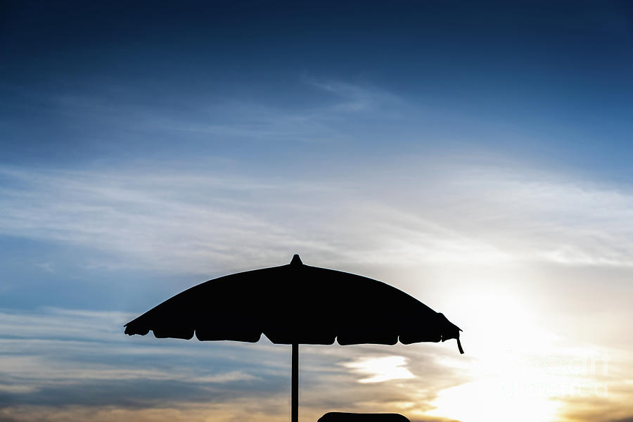 Silhouette of beach umbrella against backlight on a hot summer day. by Joaquin Corbalan