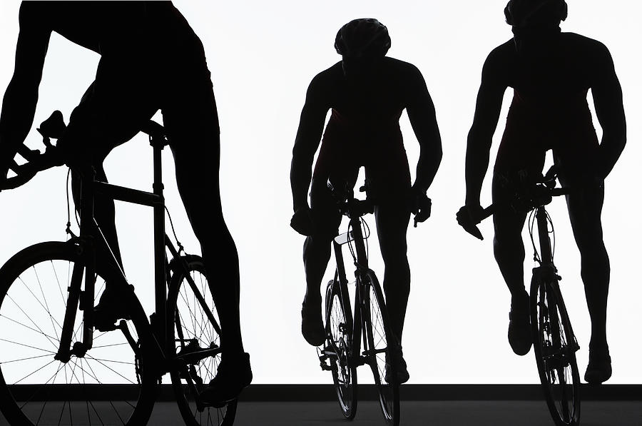 Silhouette Of Three Triathletes Riding Photograph by Paul Taylor