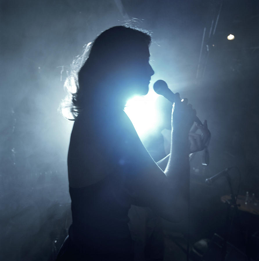 Silhouette Of Woman Using Microphone Photograph by Frank Herholdt