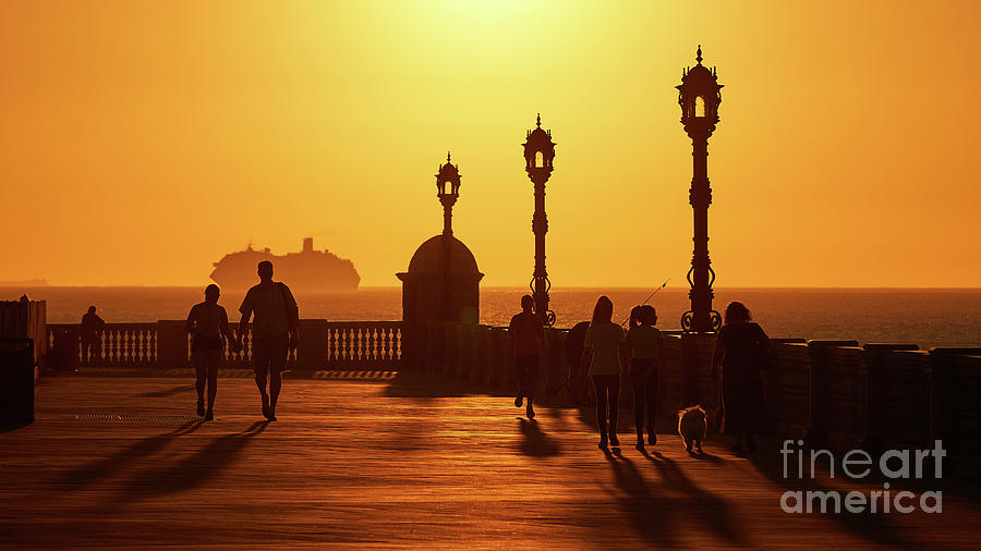Silhouetted People Walking on Boardwalk with Cruiser at Sunset by Pablo Avanzini