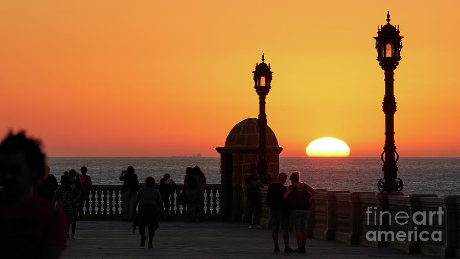 Silhouetted People Walking on Boardwalk with the Sun Setting by Pablo Avanzini