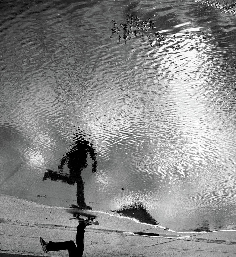 Skateboarder Reflection In Puddle Photograph by Mgs