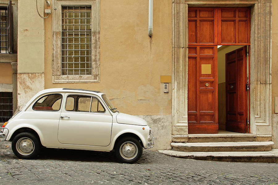 Small Coupe Parked Near A Doorway On A Photograph by S. Greg Panosian
