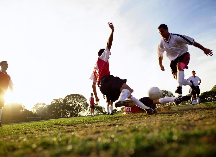 Soccer Players Tackling For Ball Photograph by Ryan Mcvay