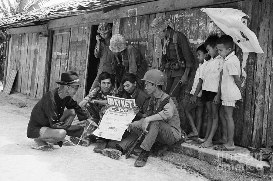 Soldiers And Villagers Read Paper Photograph by Bettmann