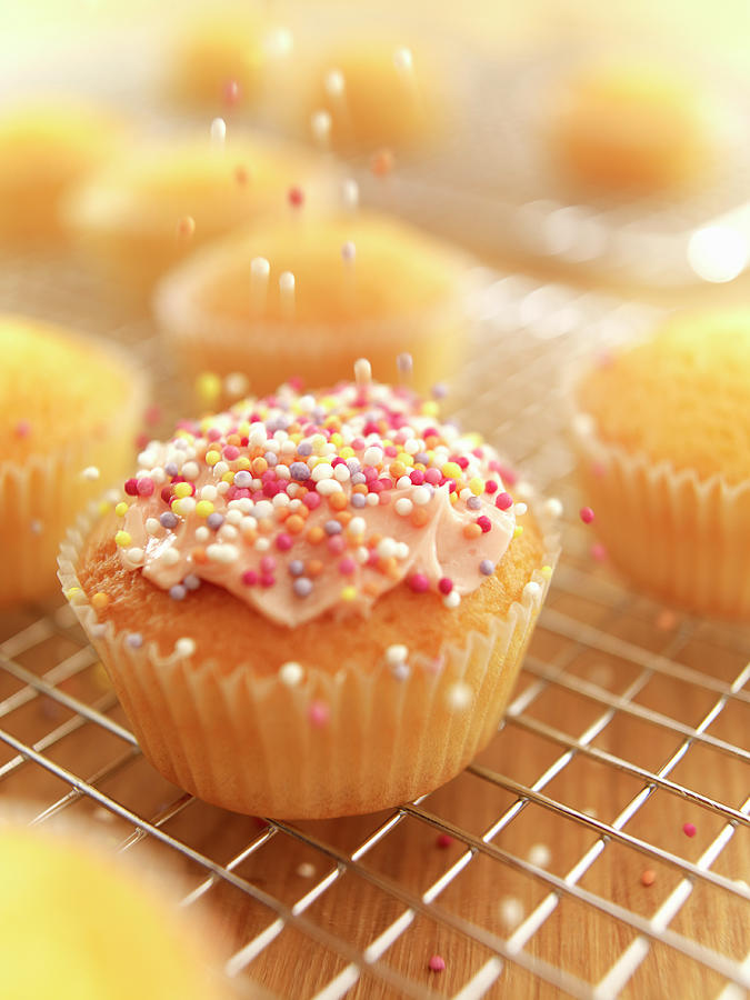 Sprinkles Falling On Frosted Cupcake Photograph by Adam Gault