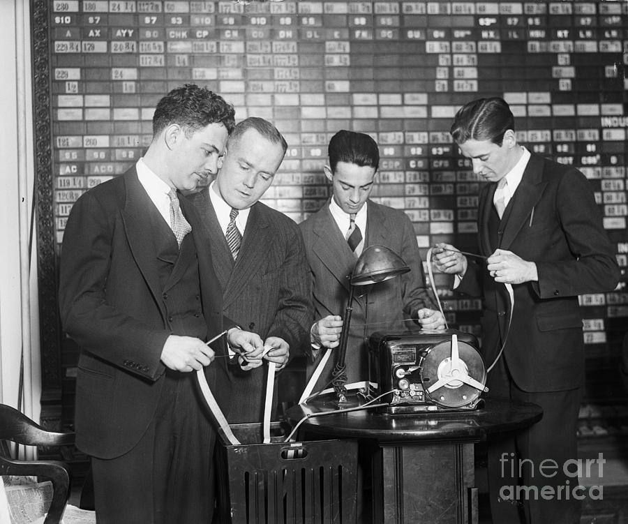 Stock Brokers Read New Ticker Tape Photograph by Bettmann