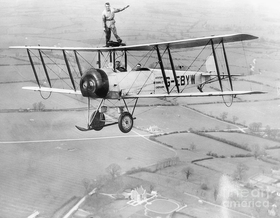 Stunt Flyer On Top Of Plane In Midair Photograph by Bettmann