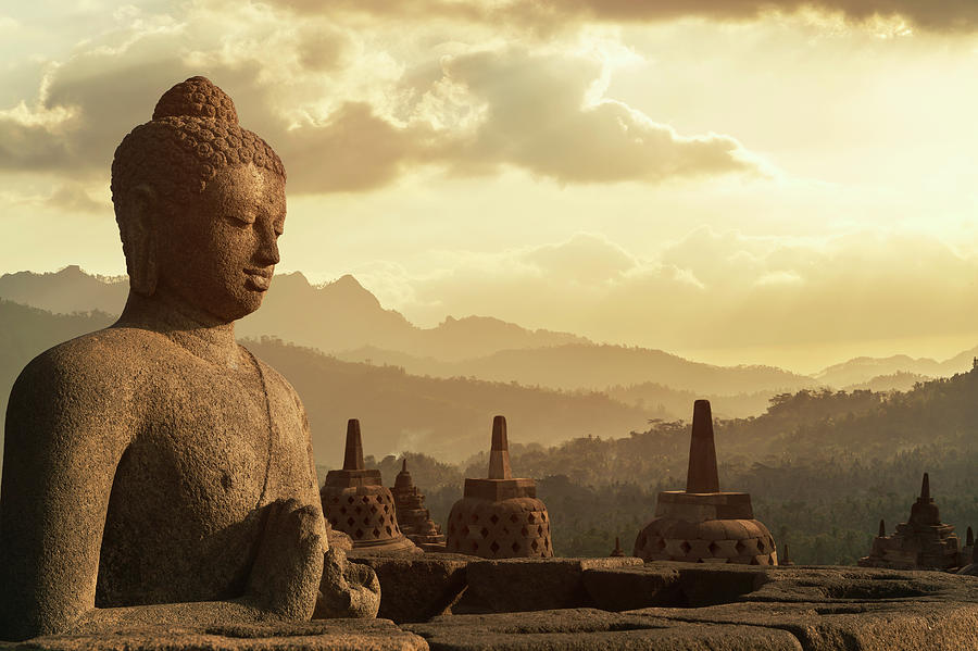 Sunset Over Buddha Statue In Borobudur Photograph by Buena Vista Images