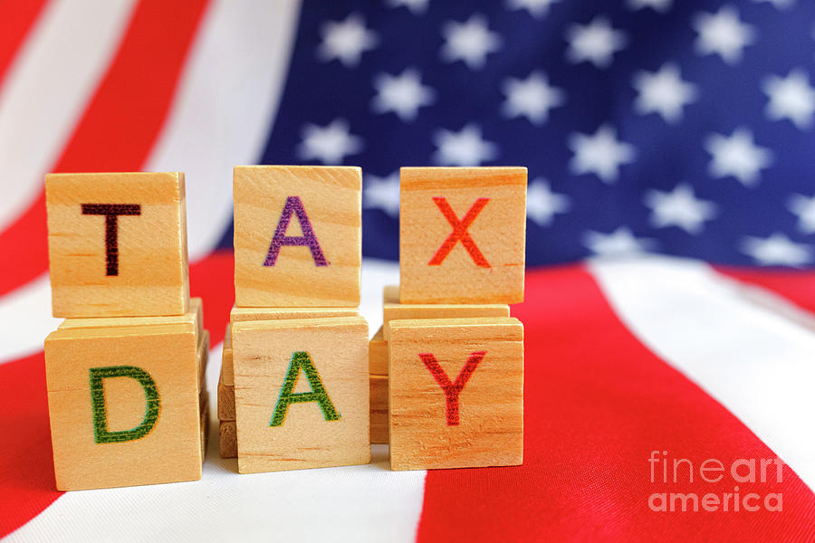 Tax day written with wooden letters to indicate the day of payment of taxes in america. by Joaquin Corbalan