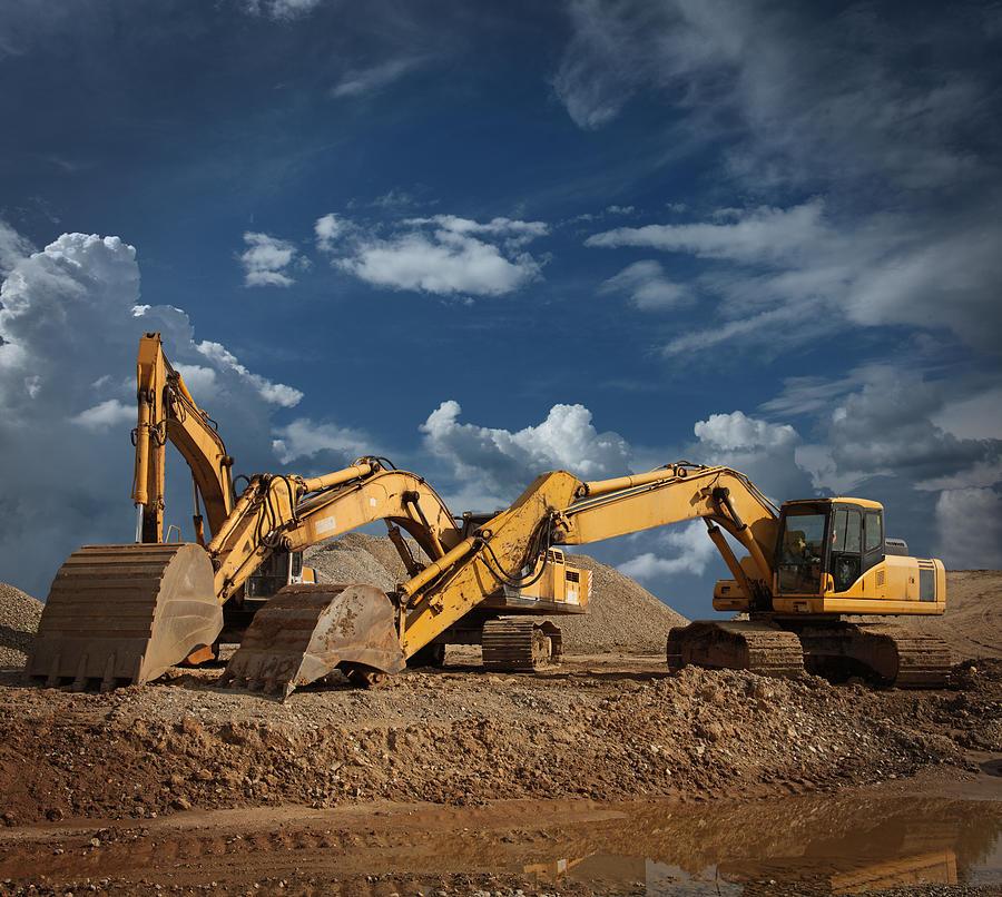 Three Excavators At Construction Site Photograph by Narvikk