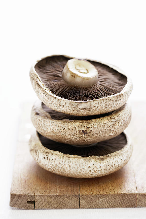 Three Flat Mushrooms In Pile On Wooden Photograph by Martin Poole