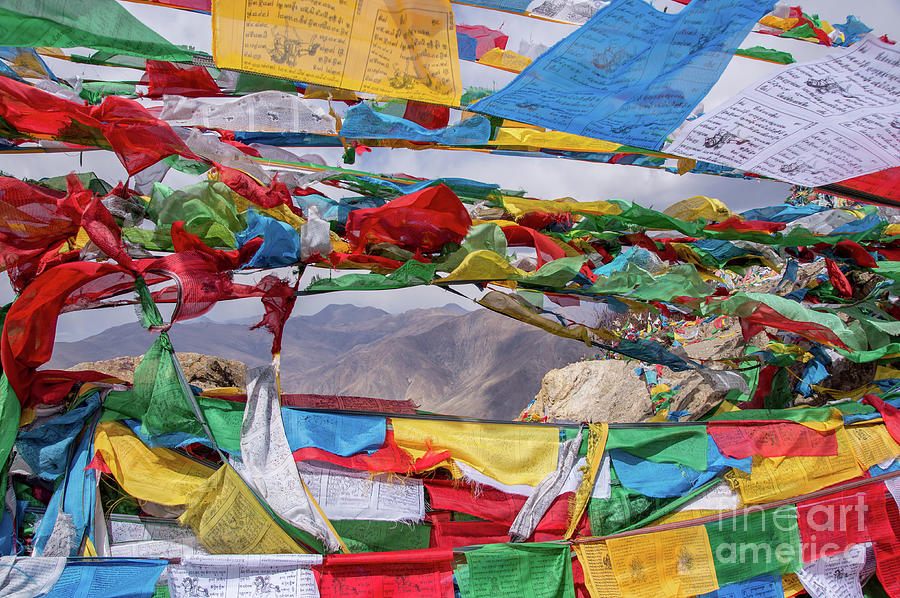 Tibetan landscape with prayer flags in foreground by Ulysse Pixel