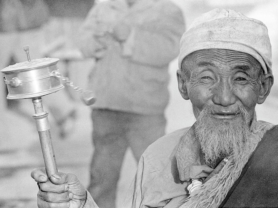 Tibetan man with prayer wheel by Neil Pankler