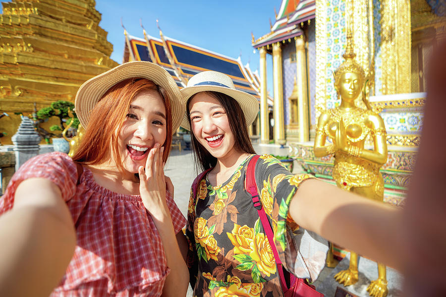 Two asian girlfriends traveling and selfie by camera in smartpho by Anek Suwannaphoom