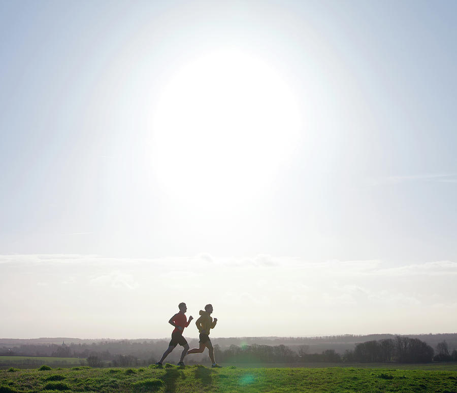 Two Joggers Running On Hill With Low Photograph by Tim Robberts
