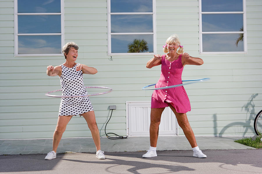 Two Senior Women Playing With Plastic Photograph by Greg Ceo