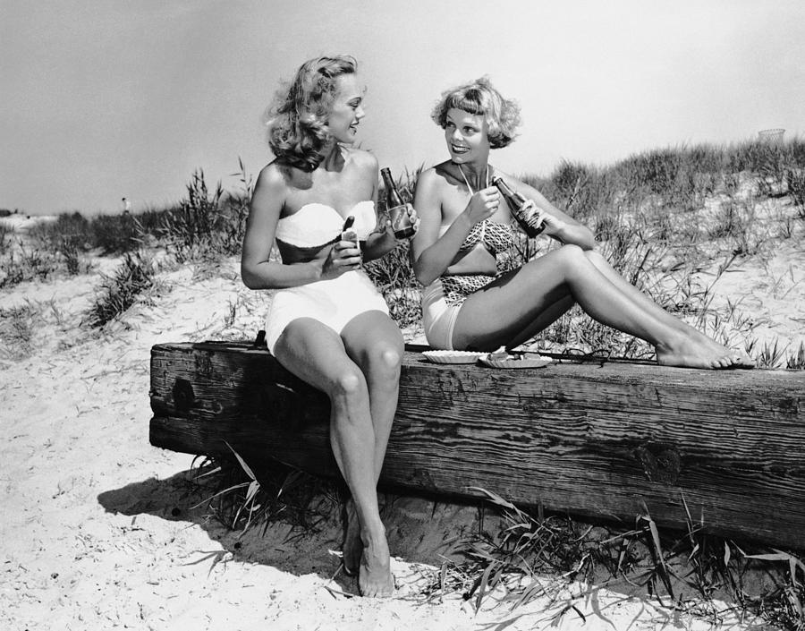 Two Women Drinking Soda On Beach Photograph by George Marks