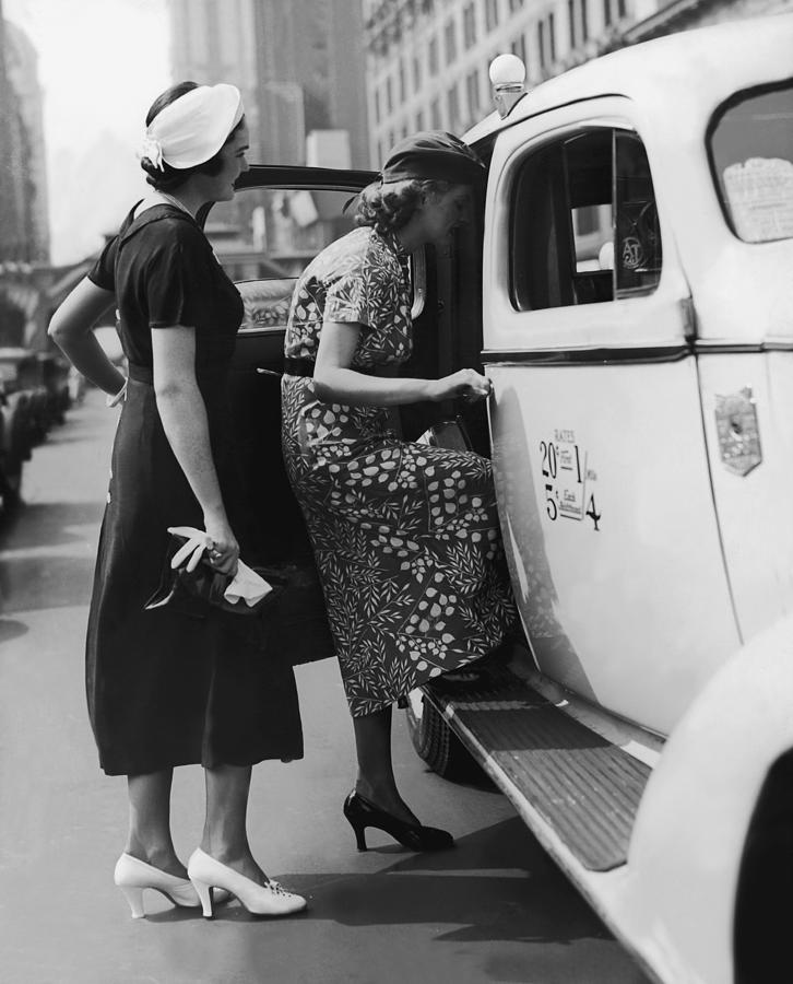 Two Women Getting In A Taxi On An Urban Photograph by Fpg