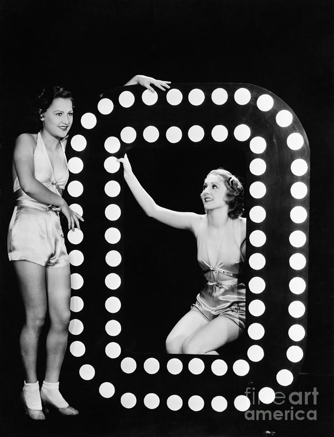 Looking Away Photograph - Two Young Women Posing With The Letter O by Everett Collection