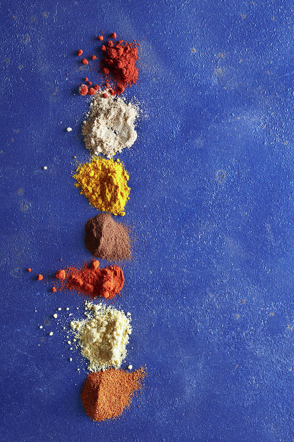 Various Spices On Blue Surface Photograph by Maren Caruso