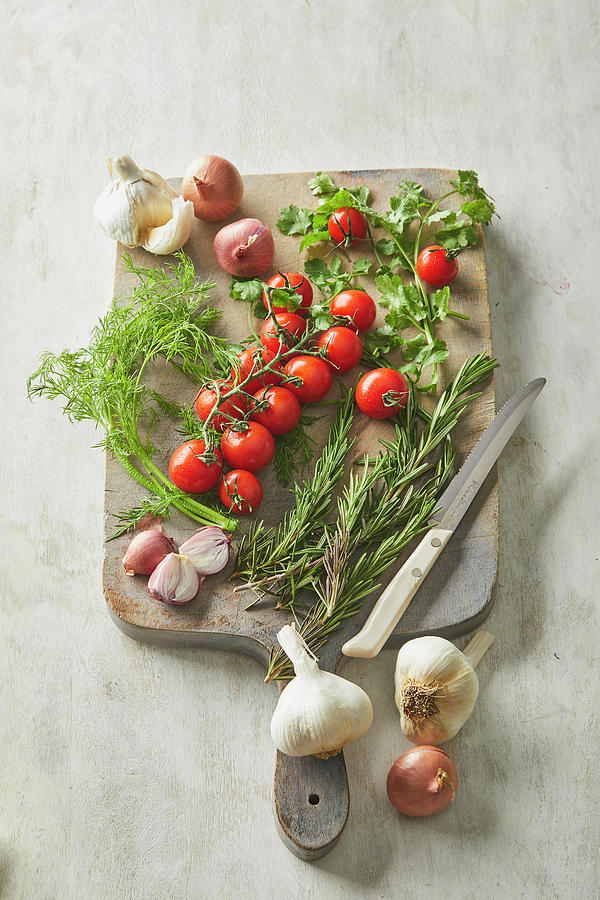 Vegetables and herbs on a cutting board by Cuisine at Home