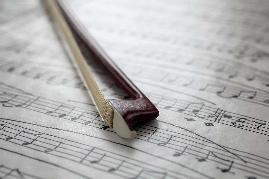Violin Bow On Music Sheet Photograph by Daniel Allan