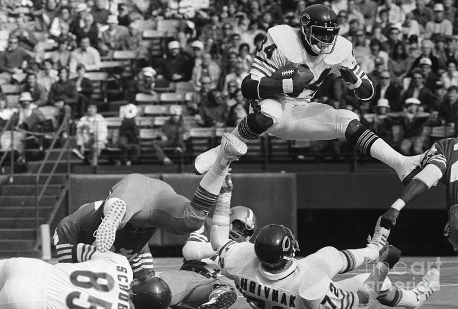 Walter Payton Jumps Over Gary Hrivnak Photograph by Bettmann