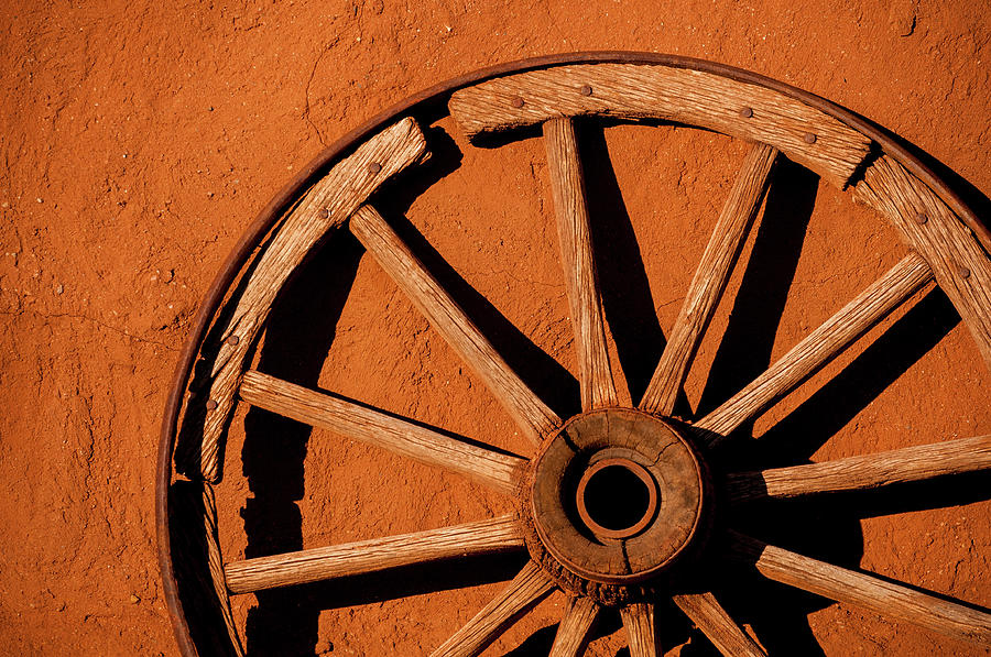 Weathered Wagon Wheel Against An Adobe Photograph by Photo By Sam Scholes