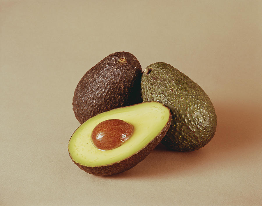 Whole And Half Avocado On Beige Photograph by Tom Kelley Archive