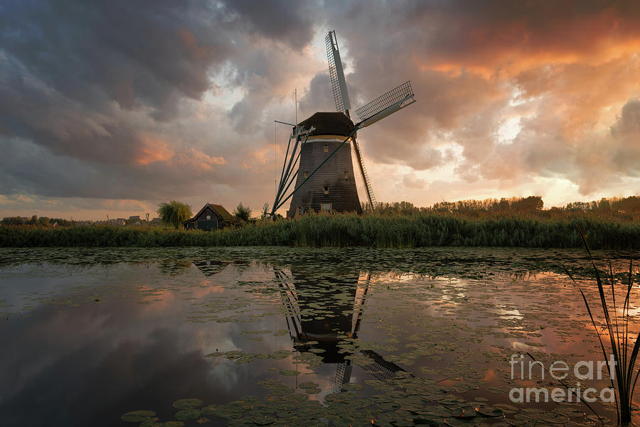 Sunset Photograph - Windmill under an explosive sky at sunset by IPics Photography