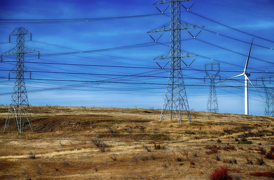 Windmills and power lines on hills  by Steve Estvanik