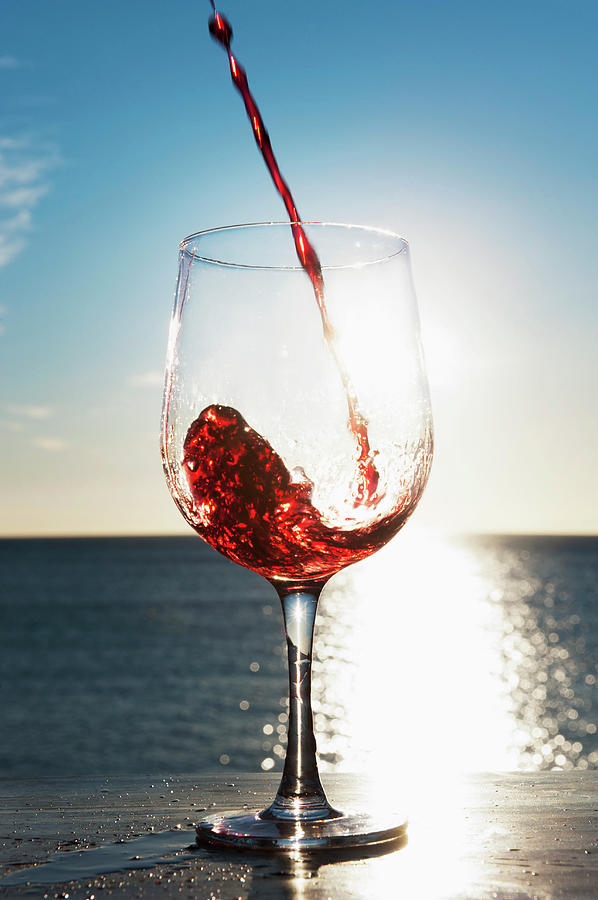 wine pouring into glass outdoors by bill holden