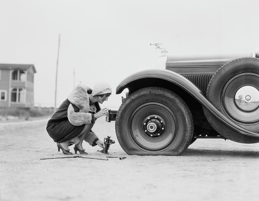 People Photograph - Woman Changing Flat Tire On Car by H. Armstrong Roberts