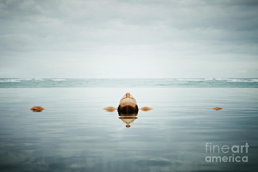 Woman Floating On Back In Infinity Pool Photograph by Thomas Barwick